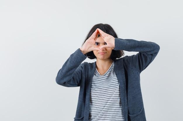 T- 셔츠, 재킷에 삼각형 제스처를 보여주는 자신감을 찾고 어린 소녀.