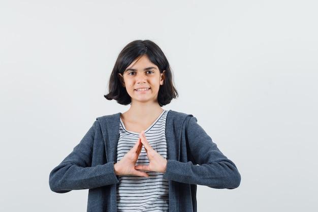 T- 셔츠, 재킷에 삼각형 제스처를 표시 하 고 행복을 찾는 어린 소녀.