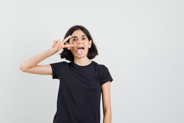 黒のtシャツで勝利のジェスチャーを示し、自信を持って見える少女。正面図。