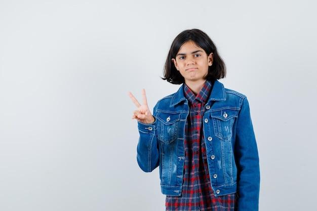 シャツ、ジャケット、自信を持って、正面図で勝利のジェスチャーを示す少女。