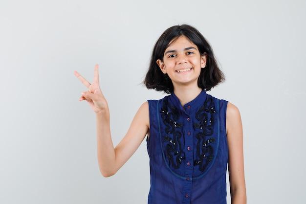 青いブラウスで勝利のサインを示し、幸せそうに見える少女。