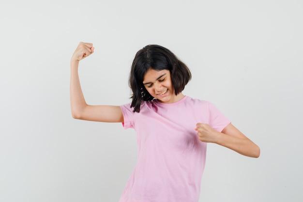 분홍색 티셔츠에 승자 제스처를 보여주는 운이 좋은 어린 소녀. 전면보기.