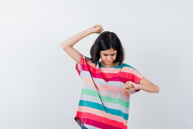 Bambina che mostra i gesti del vincitore in maglietta e sembra fortunata, vista frontale.