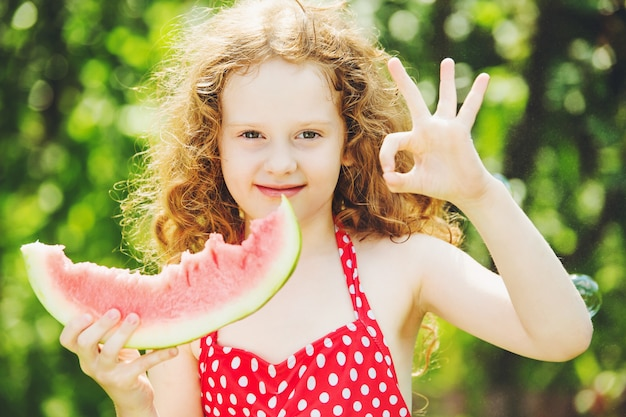 Little girl shows gesture ok and eating watermelon.