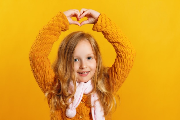 Little girl shows a heart with her hands