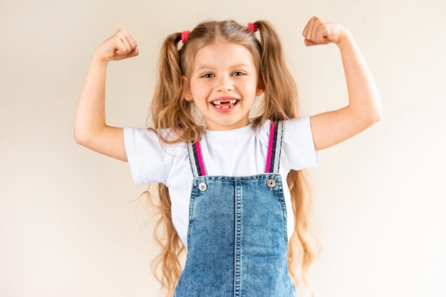 A little girl shows her biceps.