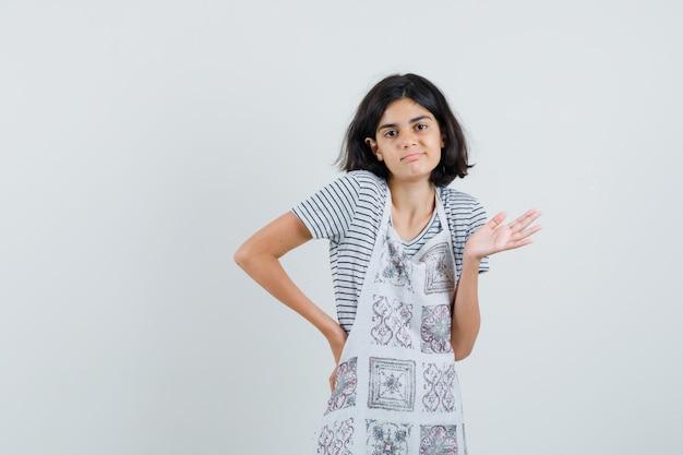 Tシャツ、エプロンに肩をすくめて、混乱しているように見える少女。