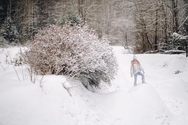A little girl in a silver jacket in winter goes outside in winter