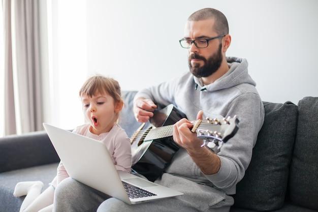 그녀의 아버지가 기타를 연주하는 동안 노래를 부르는 어린 소녀. 둘 다 노트북을 찾고 있습니다.
