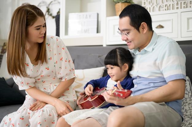 Маленькая девочка поет и играет на гитаре со своей семьей, сидя на диване у себя дома