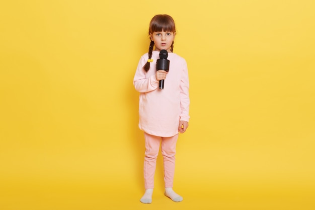 Little girl singing song with cam and serious facial expression, looks at camera with worried look, being confused to arrange performance, wearing casual attire, isolated over yellow background.