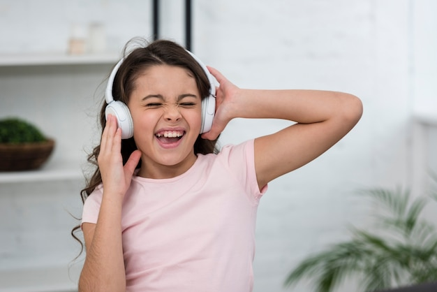 Little girl singing while listening music through headphones
