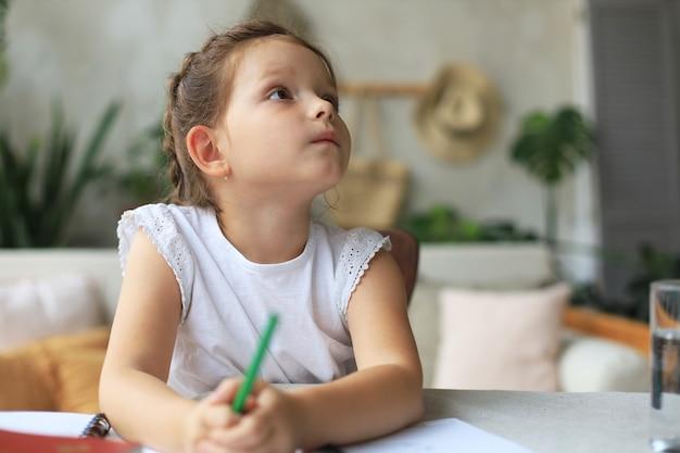 어린 소녀는 책상에 앉아 공책에 글을 쓰고 집에서 운동을 하고 어린 아이가 손으로 숙제를 준비합니다.