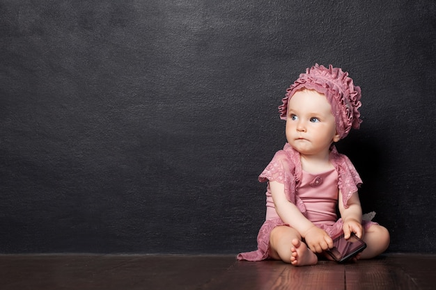 Little girl siting 1 year on a brown wooden floor.  the girl looks aside, holding phone in hand. thoughtful look. copy space