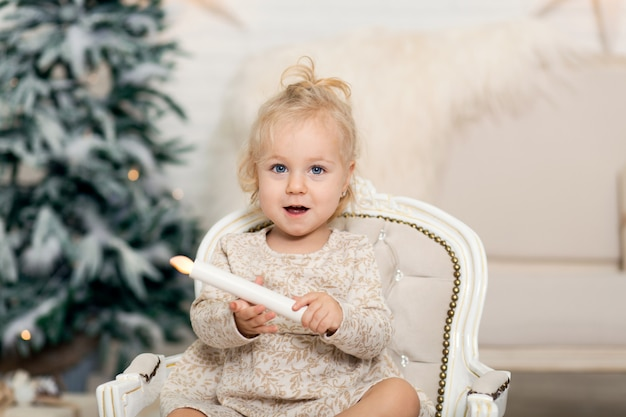 Little girl sits in the armchair and holds a candle in her hand in a room near the christmas tree