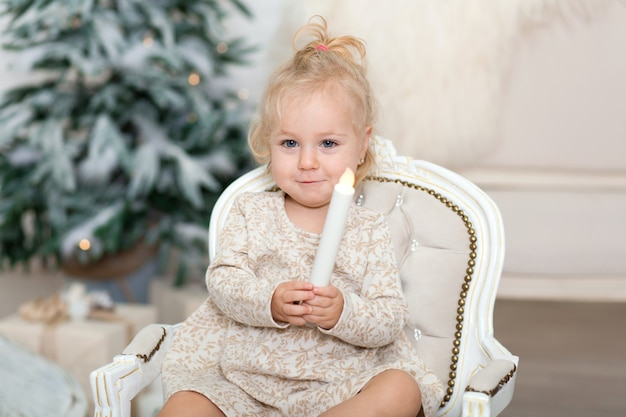 A little girl sits in the armchair and holds a candle in her hand in a room near the christmas tree