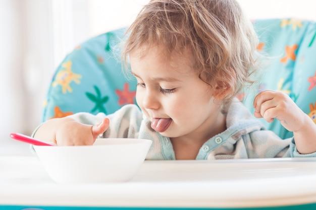 小さな女の子がテーブルに座ってスプーンで食べる