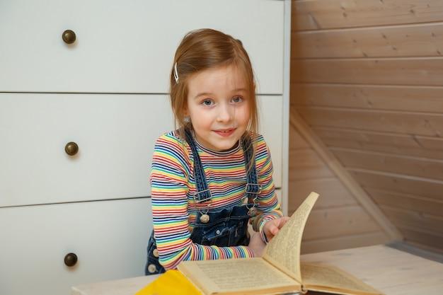 小さな女の子がテーブルに座って本をめくります