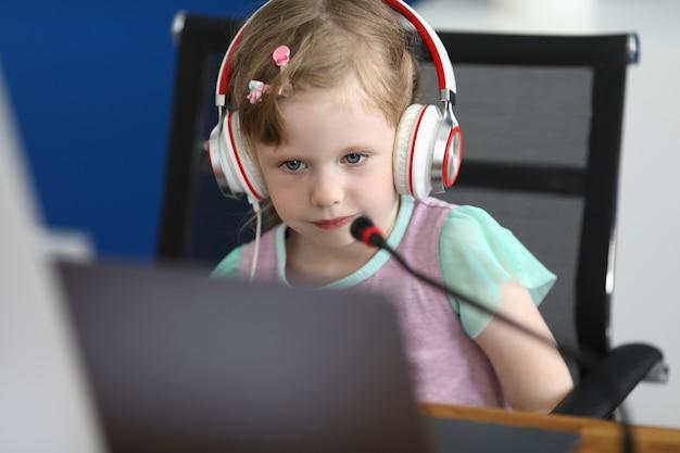 Маленькая девочка сидит за компьютером в наушниках с микрофоном