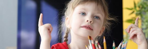 어린 소녀는 연필로 테이블에 앉아서 그녀의 손가락에 숫자를 계산합니다. 취학 전 아이 교육 개념