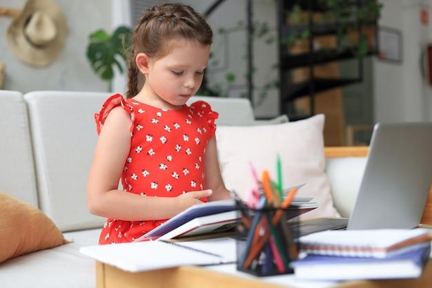 小さな女の子は家のdeslに座って、宿題、資料の自己学習、本を読んでいます。遠隔教育の概念