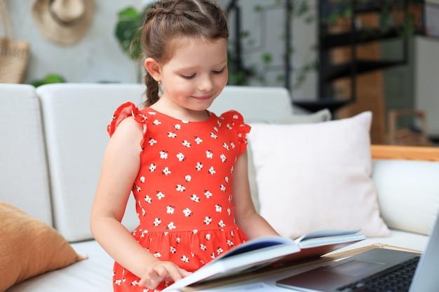小さな女の子は家のdeslに座って、宿題、資料の自習、本を読んでいます。遠隔教育の概念。