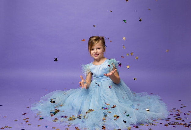 A little girl sits in a beautiful princess dress and catches confetti on purple