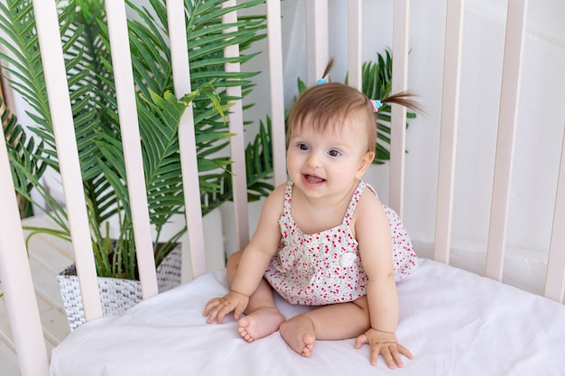 A little girl sits in a bright room in a crib and smiles