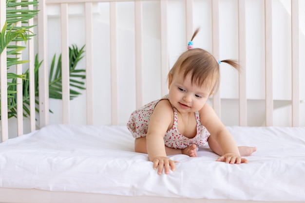 A little girl sits in a bright room in a crib