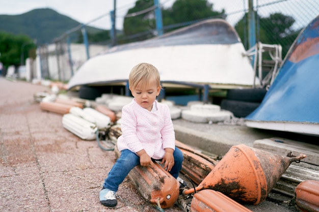 Little girl sits on a buoy on the shore