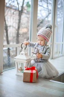 A little girl sits by the window and opens christmas presents.