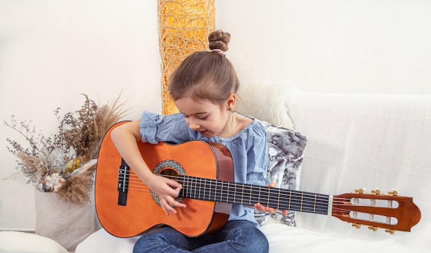 A little girl sits on the couch and plays the guitar