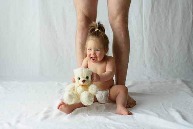小さな女の子が幸せに座っていると彼女の父の足
