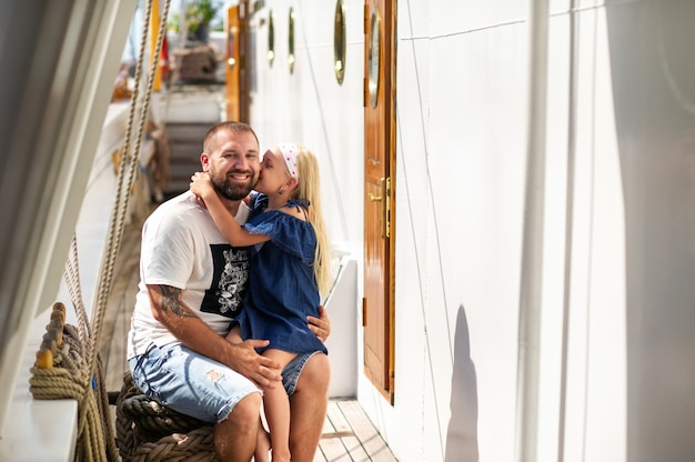 A little girl sits in her father's arms and kisses him on the cheek on the deck of a large lithuania