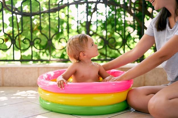 풍선 수영장에 앉아 엄마를 바라보는 어린 소녀