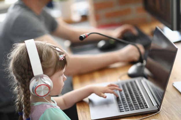Little girl sits at laptop in headphones with microphone next to man