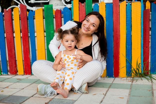 彼女の母親と一緒に色とりどりの木製のフェンスの近くに座っている少女
