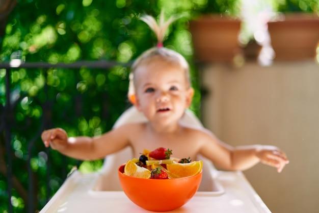小さな女の子は、果物のボウルの前のバルコニーのハイチェアに座っています