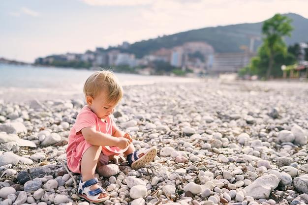 Маленькая девочка сидит на галечном пляже и играет с галькой
