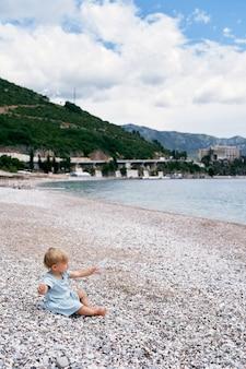 어린 소녀는 손에 물 한 병을 들고 바다 옆 자갈 해변에 앉아 있다