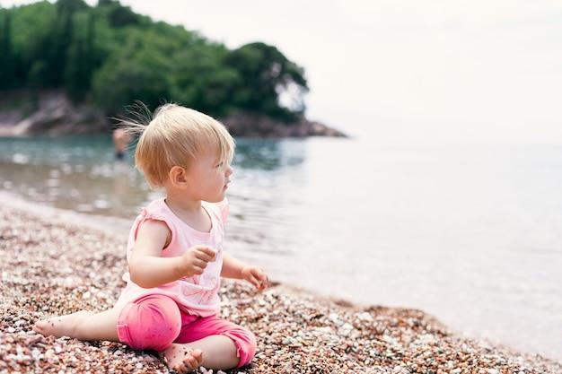 어린 소녀는 녹색 섬을 배경으로 물 근처의 조약돌 해변에 앉아 있습니다.