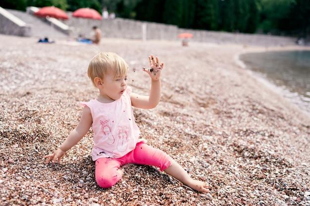 어린 소녀는 물 근처 자갈 해변에 앉아 자갈을 던졌습니다