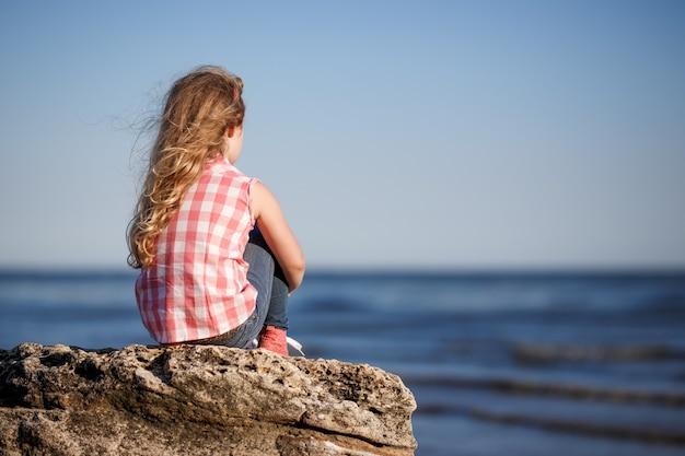 少女は岩の多い海岸に座って海を見ています。