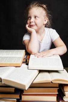 Little girl sits on a pile of books and dreams. education and training.