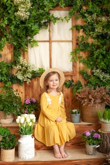 A little girl sits on porch of wooden house, around green houseplants and flowers. kid is in yellow dress, straw hat. concept of childhood. gardening. rustic terrace, porch. child playing in backyard