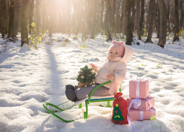 A little girl sits in a sled in the winter forest with gifts and a small christmas tree