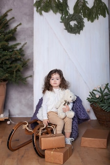 Little girl sits in sleigh and holds gift in hands