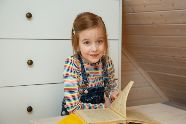 Little girl sits at a table and leafs through a book