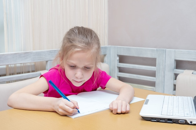 A little girl sits at a table with a laptop and writes homework in a notebook