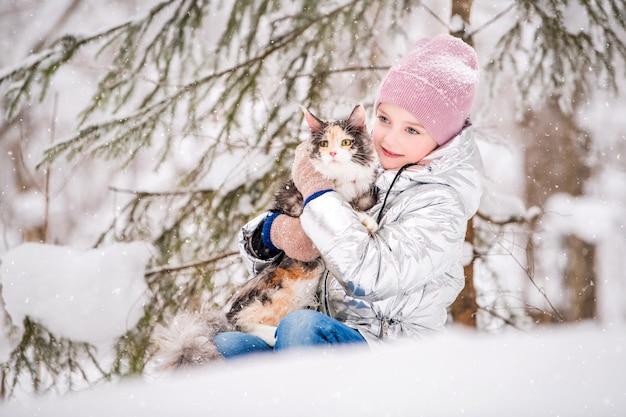 冬の森の雪の中で抱擁で猫と一緒に座っている少女